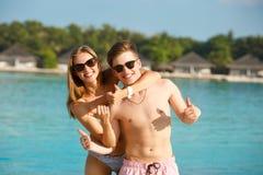 Lyckliga barnpar har gyckel och kopplar av på stranden Man- och kvinnashowtummar som tycker om upp semester nära havet bungalower Arkivbild