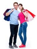 Lyckliga barnpar med shoppingpåsar Arkivfoton
