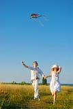 Lyckliga barnpar som flyger en drake royaltyfri fotografi