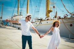 Lyckliga barnpar som går vid hamnen av ett touristic hav, tillgriper arkivfoton