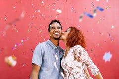 Lyckliga barnpar som lite varstans firar med konfettier Royaltyfria Bilder