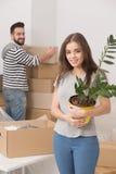 Lyckliga barnpar som packar upp askar och flyttning in i ett nytt hem arkivbilder