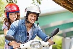 Lyckliga barnpar som rider en sparkcykel Royaltyfri Foto