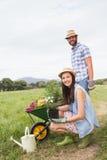 Lyckliga barnpar som tillsammans arbeta i trädgården Royaltyfria Bilder