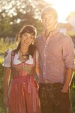 Lyckliga bavarianpar i aftonsolen Royaltyfri Foto