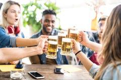Lyckliga blandras- vänner som tillsammans dricker och rostar öl på bryggeristången - kamratskapbegrepp med ungdomarsom har gyckel royaltyfria bilder