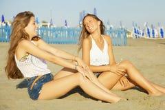 Lyckliga blonda tonåringbästa vän som sitter på att skratta för strand Royaltyfri Foto