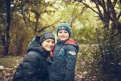 Lyckliga bröder i höstskogfoto Arkivfoto