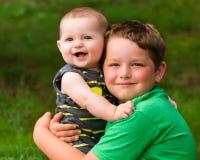 Lyckliga bröder som kramar i sommarstående royaltyfri foto