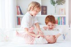 Lyckliga bröder som spelar med det lilla spädbarnet för att behandla som ett barn systern hemma royaltyfri bild