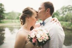 Lyckliga brölloppar som kramar och ler sig på bakgrundssjön, skog Royaltyfri Foto
