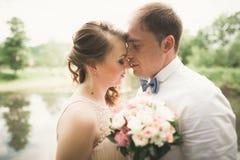 Lyckliga brölloppar som kramar och ler sig på bakgrundssjön, skog Arkivfoto