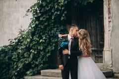 Lyckliga brölloppar som kramar och ler sig på de ursnygga växterna för bakgrund i slott royaltyfria foton