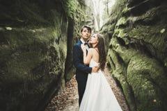 Lyckliga brölloppar som kysser och kramar nära en hög klippa arkivbilder
