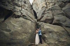 Lyckliga brölloppar som kysser och kramar nära en hög klippa fotografering för bildbyråer