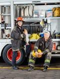 Lyckliga brandmän med lastbilen på brandstationen Royaltyfri Fotografi