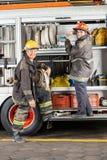Lyckliga brandmän som står med lastbilen på brandstationen Arkivbilder