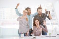 Lyckliga businesspeople i deras kontor royaltyfri fotografi