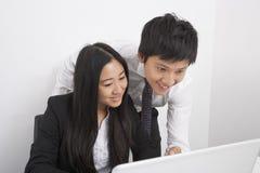 Lyckliga businesspeople som i regeringsställning diskuterar över bärbara datorn Arkivfoto