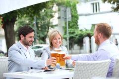 Lyckliga businesspeople som rostar ölexponeringsglas på den utomhus- restaurangen Royaltyfri Bild
