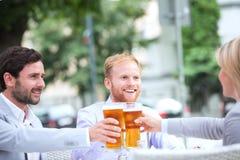 Lyckliga businesspeople som rostar ölexponeringsglas på den utomhus- restaurangen arkivbild