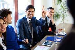 Lyckliga businesspeople som sitter på tabellen royaltyfri bild