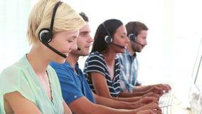 Lyckliga call centermedel som talar på hörlurar med mikrofon stock video