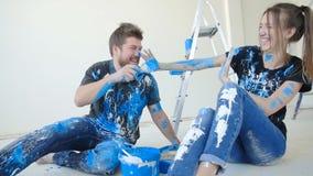 Lyckliga charmiga par som har gyckel och målar ett rum i deras nya hus
