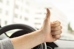 Lyckliga chaufförvisningtummar upp i bil royaltyfria bilder
