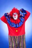 Lyckliga clownmän på blå bakgrund Arkivfoto