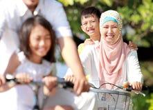 Lyckliga cyklar för muslimfamiljridning Fotografering för Bildbyråer