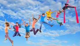 Lyckliga dansbanhoppningbarn i himmel Fotografering för Bildbyråer