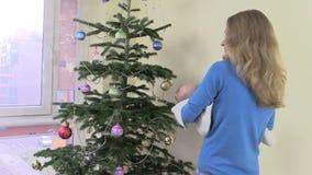 Lyckliga den nyfödda modervaggan behandla som ett barn i händer nära julgranen lager videofilmer