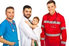 Lyckliga doktorer med behandla som ett barn pojken Royaltyfria Bilder