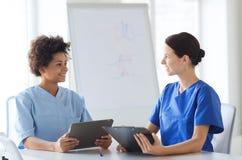 Lyckliga doktorer med minnestavlaPC:n som möter på sjukhuset royaltyfri fotografi