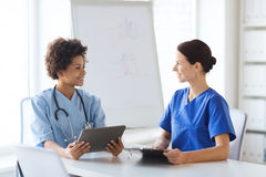 Lyckliga doktorer med minnestavlaPC:n som möter på sjukhuset royaltyfria bilder