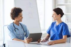 Lyckliga doktorer med minnestavlaPC:n som möter på sjukhuset royaltyfria foton