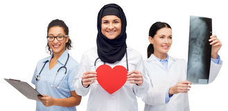 Lyckliga doktorer med röd hjärta, röntgenstrålen och skrivplattan Royaltyfria Foton