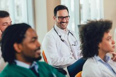 Lyckliga doktorer p? seminarium i h?rsal p? sjukhuset royaltyfri bild