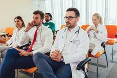 Lyckliga doktorer p? seminarium i h?rsal p? sjukhuset royaltyfri fotografi