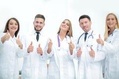 Lyckliga doktorer som ler upp och visar tummar arkivfoton