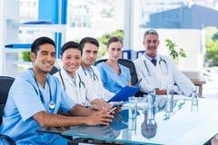Lyckliga doktorer som ser kameran, medan sitta på en tabell arkivfoton