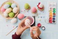Lyckliga easter! Ägg för en påsk för kvinnahandmålning Royaltyfria Bilder