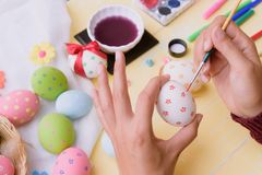 Lyckliga easter! Ägg för en påsk för kvinnahandmålning Royaltyfri Bild