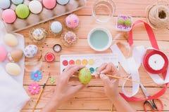 Lyckliga easter! Ägg för en påsk för kvinnahandmålning Arkivbilder