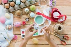 Lyckliga easter! Ägg för en påsk för kvinnahandmålning Lycklig familjpr royaltyfri bild