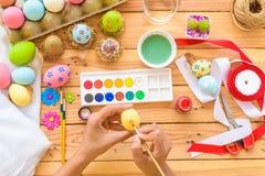 Lyckliga easter! Ägg för en påsk för kvinnahandmålning Lycklig familjpr Arkivbild