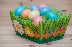 Lyckliga easter ägg i en korg på det trä Arkivfoton