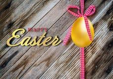 Lyckliga easter, ägg med den guld- och röda och svarta pilbågen Royaltyfri Fotografi