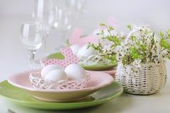 lyckliga easter Dekor- och tabellinställningen av påsktabellen är en vas med rosa tulpan och disk av rosa och grön färg fotografering för bildbyråer